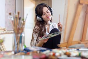 Chica pintando mientras escucha audiolibros de literaudio